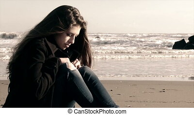 female teenager on the beach crying