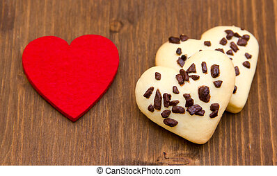 Biscuits and red little heart on wooden table