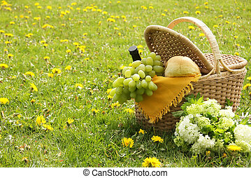 Picnic basket with french bread, grapes and wine.