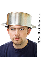 serious man with stew pan on head - Face of young serious...