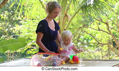 child play with toys sitting beside her mother
