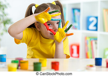 cute kid have fun painting her hands - cute kid girl have...