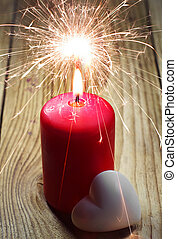 Burning candle and heart on a wooden table