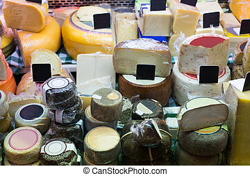 Market counter with different cheese kinds close up
