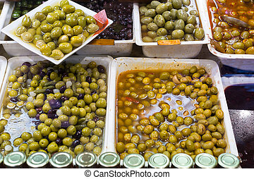 Many fresh and pickled olives at shop stand close up