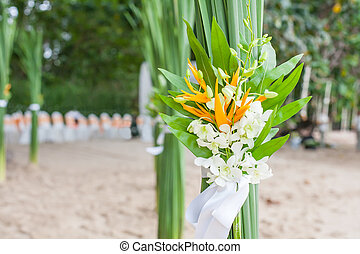 Floral arrangement at a wedding ceremony on the beach. -...