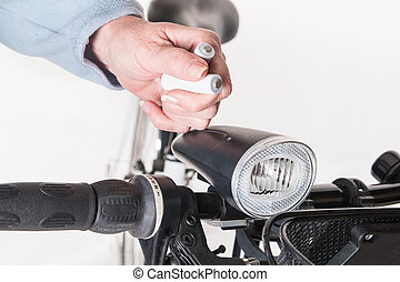 Replace the battery in the front lamp on bicycle wheel -...