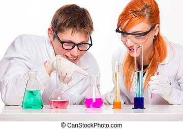 Two students in chemistry lab doing reactions - Students in...