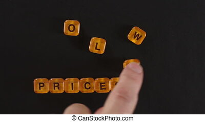 Letter Blocks Spell Lower Prices - A close up shot of a man...