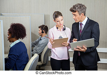 Business People With Clipboard And Laptop Discussing In Call Cen