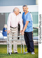 Smiling Caretaker Assisting Senior Man To Use Walking Frame