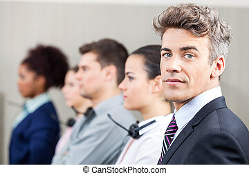 Confident Manager With Employees Standing In Row - Portrait...