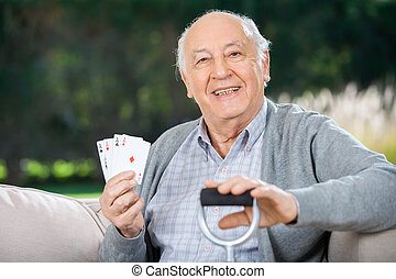 Senior Man Holding Four Aces While Sitting On Couch -...