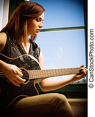 Young woman playing acoustic guitar