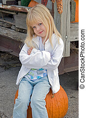 Country Bumpkin - Little blond girl on a pumpkin
