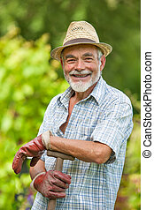 Senior gardener with a spade - Portrait of a smiling senior...