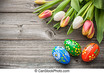 Easter eggs and fresh spring tulips on weathered wooden...