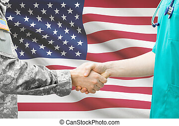 Soldier and doctor shaking hands with flag on background -...