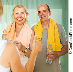 Elderly couple talking to trainer - Smiling senior spouses...