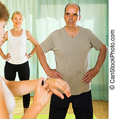 Mature couple with trainer at gym