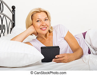 mature woman resting with ereader on bed