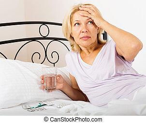female pensioner taking medicine - Serious female pensioner...