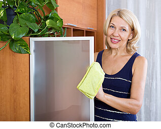 Mature woman dusting glass - Happy mature woman dusting...