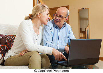 Smiling mature couple with laptop at table in home