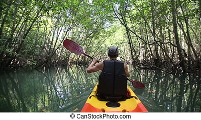 man boating in kayak along lagoon - elder man boating in...