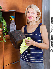 Mature houswife dusting wooden furniture - Mature smiling...