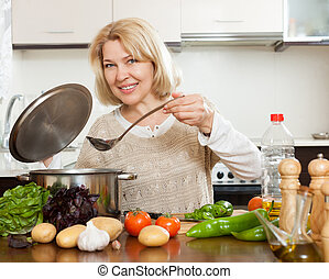 Smiling mature woman cooking  soup