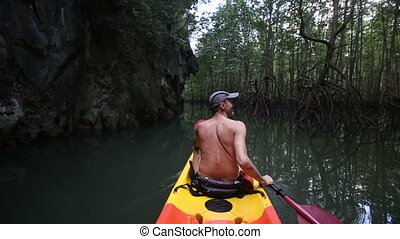 man boating in kayak along lagoon - topless elder man rowing...