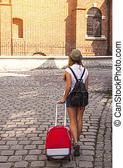 Young cute girl travels through the cities of old Europe An...
