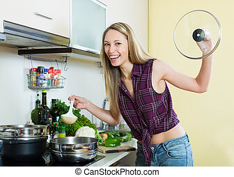 Woman cooking soup - Smiling long-haired beautiful woman...