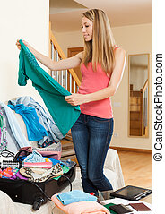 Girl packing luggage - Long-haired girl standing near...