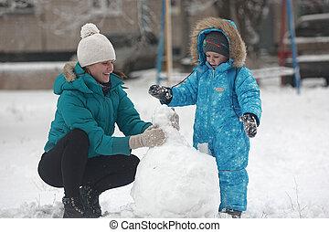 family sculpts snowman