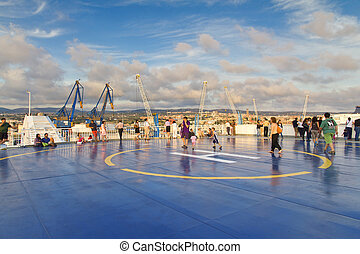 Tourists in Helipad for helicopter on the upper deck of big...