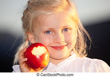 Child outside with healthy vitamine rich red apple - Child...