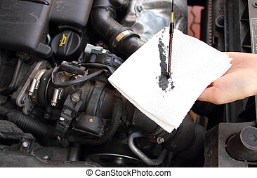Auto mechanic checks the oil level in a car engine