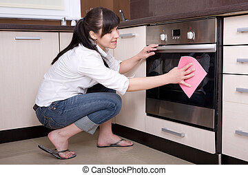 house work - attractive young woman cleaning kitchen