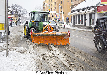 Clearing roads of snow - Snowplow tractor removing snow from...