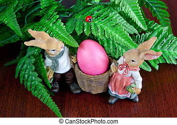 Rabbits and Easter eggs - Two rabbits carrying Easter egg on...
