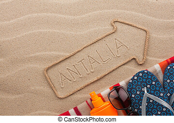 Antalya pointer and beach accessories lying on the sand, as...