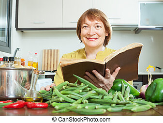 mature woman cooking okra with  cookery book