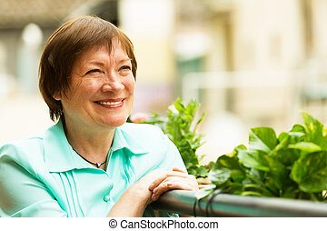 Female pensioner resting at balcony with flowers and smiling