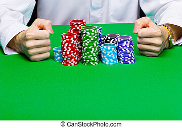 Man with a bunch of chips. Green table