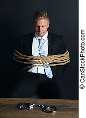 Businessman Tied With Rope Sitting In Front Of Table -...