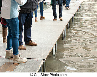 People walking on catwalk in Venice during the high tide