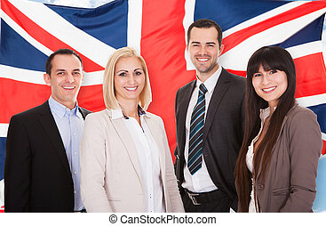 Group Of Happy Businesspeople Standing In Front Of British...