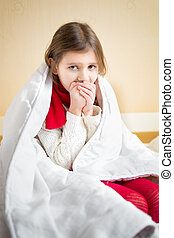 sick little girl coughing on bed under blanket - Portrait of...